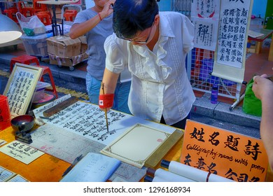 Malaysia, Malacca - November, 2018 :  a disabled woman can do Calligraphy name with poem  in Jonker walk (jonker street),  Melaka, Malaysia