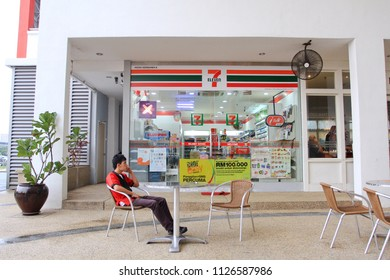 MALAYSIA OCTOBER 2011 - Man sitting on the white chair in front of the seven eleven convenient store during hot day in Kuala Lumpur
