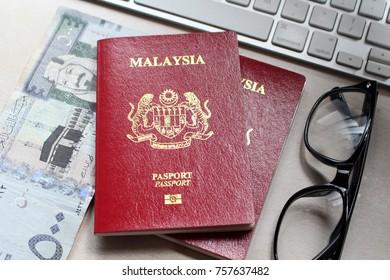 Malaysia red passport with Saudi Arabia Money
