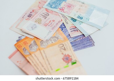 Malaysia Ringgit and Singapore Dollar notes on white background.