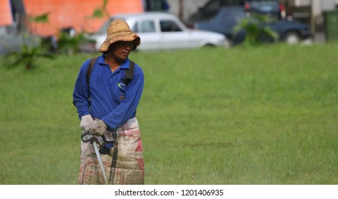 MALAYSIA, SABAH - NOVEMBER 2010: An unidentified man uses a string mower to cut grass.