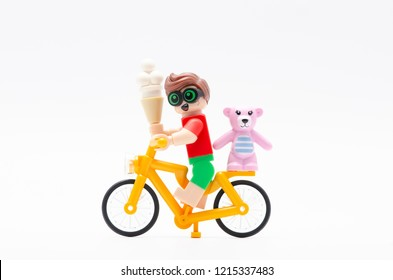 MALAYSIA, sept 30, 2018. lego robin riding bicycle with teddy bear at his back and holding a ice cream. Lego minifigures are manufactured by The Lego Group.