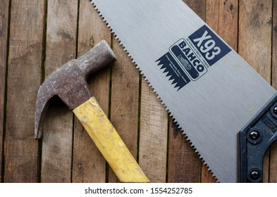 Malaysia,Marang-20 Jun 2019: A flatlay of hammer and saw over the wooden background