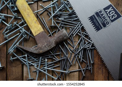 Malaysia,Marang-20 Jun 2019: A flatlay of hammer, saw and nails over the wooden background