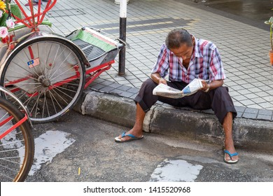 Malaysia,May 24, 2019:Man reads a newspaper on footpath at Penan