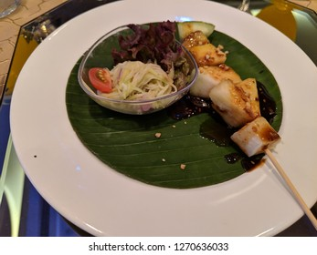 Malaysian delicacy appetizer rojak skewer with pineapple, jicama, and cucumbers with a shrimp paste sauce drizzled over and a bowl of Thai mango salad made with fish sauce and vinegar