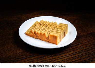 Malaysian dish Kek Lapis Sarawak or Sarawak layered cake over wooden background. Similar cake in Indonesia also known as Kek Lapis Legit or Legit Layerd Cake