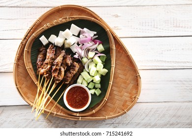 Malaysian famous food satay on bamboo basket with the cucumber and ketupat