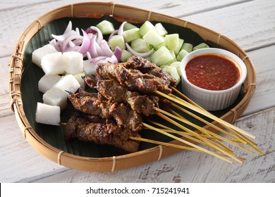 Malaysian famous food satay on bamboo basket with the cucumber and keupat