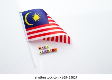 """Malaysian flag with alphabet dice assemble to spell malay words """" Hari Merdeka"""". Hari Merdeka means independent day in english"""