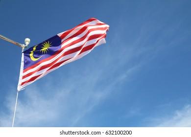 Malaysian flag flying against blue sky