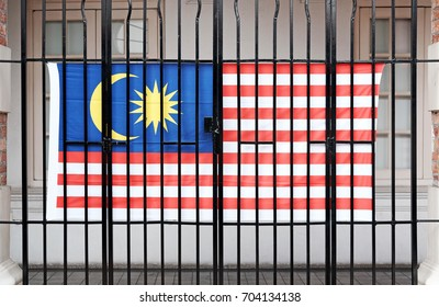 A Malaysian flag hanging on a metal grille.