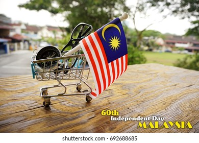 A Malaysian flag, a spectacles and a compass in the blue cart on a wooden background. Concept for 60th year of Malaysian Independence Day with wording Happy 60th Independence Day Malaysia.