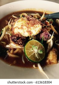 Malaysian food, mee rebus or potatoes curry noodle with lemon slice in pastel plate