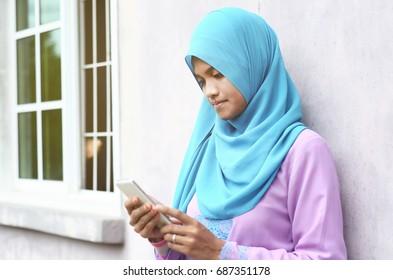 Malaysian girl with hijab looking down at smart phone.