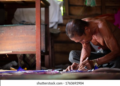 Malaysian kite maker working on a kite in his workshop in low light. Copy space text
