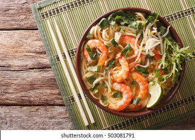 Malaysian laksa soup with shrimps, noodles and herbs close up in a bowl on the table. horizontal view from above