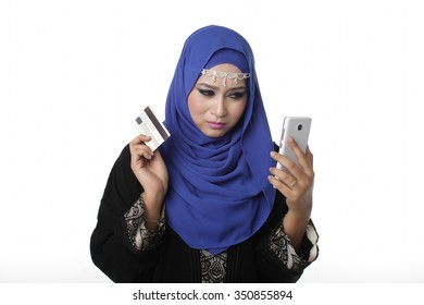 Malaysian malay asian woman using a smart phone or cell phone to shopping online