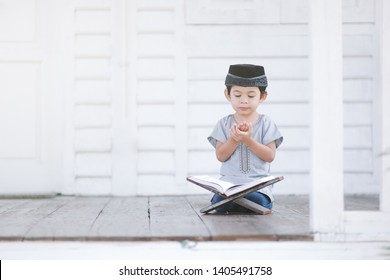 Malaysian muslim boy / toddler pray a Dua after  reciting al Quran at beautiful white wooden house with a copy space in Ramadan fasting month