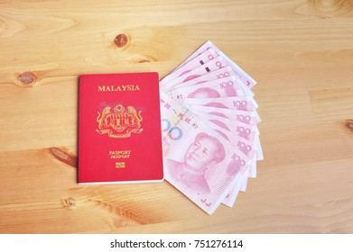 Malaysian passport and Chinese yuan notes on top of a wallet on a wooden table. Travel and vacation conceptual.