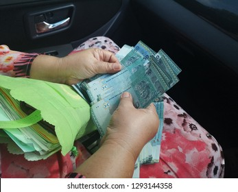 Malaysian ringgit (MYR), Malaysia money, Women counting money currency of Malaysia. Exchange money for Malaysian ringgit (MYR), business and finance concept