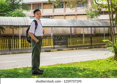 malaysian secondary school boy going to school with full set of unifiorm, green pants and black shoes, full body length. concept of high school education