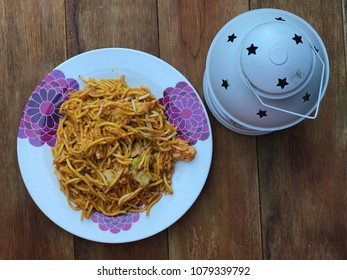 Malaysian style fried noodle or local tongue call mee goreng with lantern on wooden table