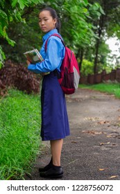 Malaysian teenage female student with school uniform walking to the school with in a greeny path and trees at the background