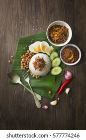 "Malaysian traditional food ""Nasi Lemak"" on rustic wooden table top. Overhead view."