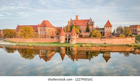 Malbork castle autumn panorama with reflection, at sunset