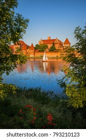 Malbork Castle at sunset in Poland, view across the Nogat river, Order of the Teutonic Knights fortified monastery, dating back to the 13th century.