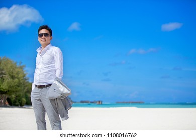 MALDIVES 2014 - Handsome man is standing on the white sand beach wearing white shirt and grey long pants in Lux resort Maldives