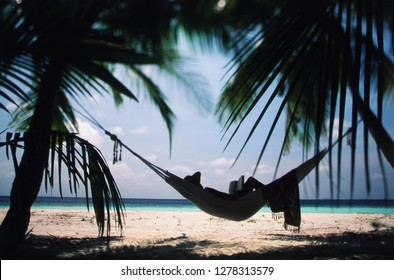 Maldives, Ari Atoll, Young woman reading book on Hammock