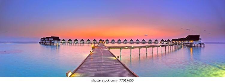 Maldives bungalows sunset panorama