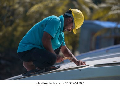 Maldives- Dec 2 2017: A worker trying to fix a roof