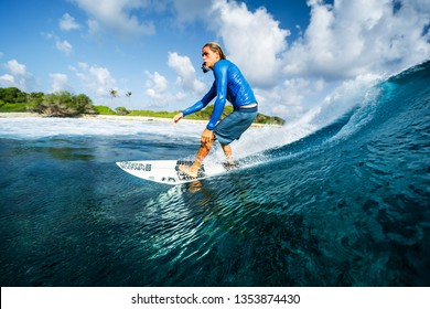 MALDIVES / HURAA - 22 MARCH 2019: Young man rides the ocean wave with camera in his mouth at famous Honkys surf spot in the Maldives