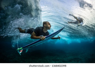 MALDIVES / HURAA - 23 MARCH 2019: Male surfer dives under the wave with his surfboard and shows the Shaka sign