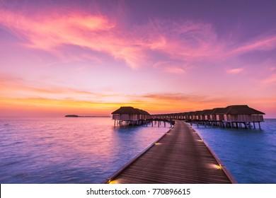 Maldives island sunset. Water bungalows resort at islands beach. Indian Ocean, Maldives