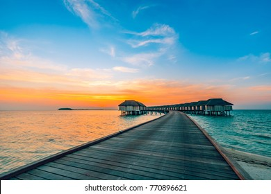 Maldives island sunset. Water bungalows resort at islands beach. Indian Ocean, Maldives