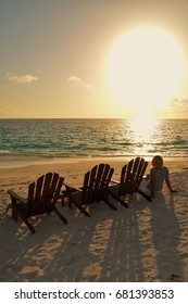 Maldives, July 8. Young blond woman sitting next to deckchair on the beach of a tropical Island, wating for sunset.. MALDIVES, JULY 8,2017