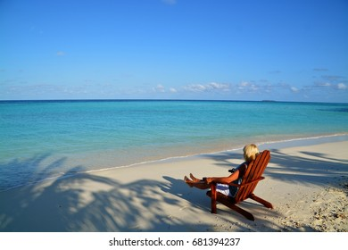 Maldives, July 8. Young blond woman sitting on a deckchair enjoying the sun on a tropical island. MALDIVES, JULY 8,2017