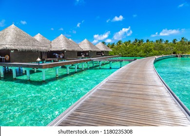 MALDIVES - JUNE 24, 2018: Water Villas (Bungalows) and wooden bridge at Tropical beach in the Maldives at summer day