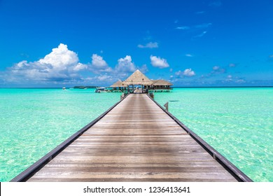 MALDIVES - JUNE 24, 2018: Water Villas (Bungalows) and wooden bridge at Tropical beach in the Maldives at summer evening