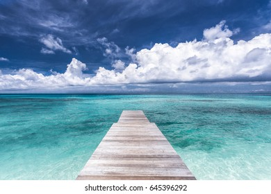 Maldives. Perspective view of a wooden pier. Moody blue sky and blue lagoon.