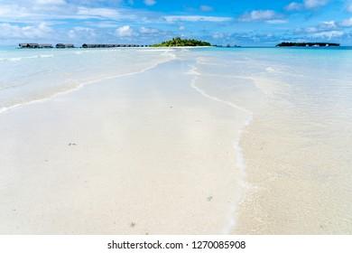 Maldives sandbank with island and water villas in background