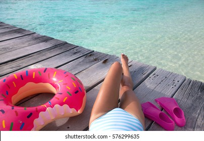 Maldives tropical summer holiday concept, woman wearing swimsuit lying down on wooden pier by the beach