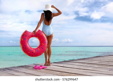 Maldives tropical summer holiday concept, woman wearing swimsuit standing on wooden pier by the beach