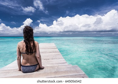 Maldives. Woman sitting on the wooden pier. Moody blue sky and blue lagoon.