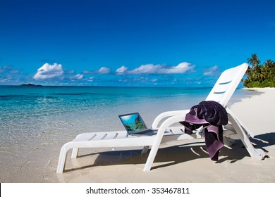 Maldivian tropical beach with mobile computer and towel on chair. Beach laptop as mobile office. Tropical seascape with notebook