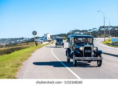 Maldonado, Uruguay - 21 July 2018: Participants of the winter parade of vintage cars entering the city of Punta del Este